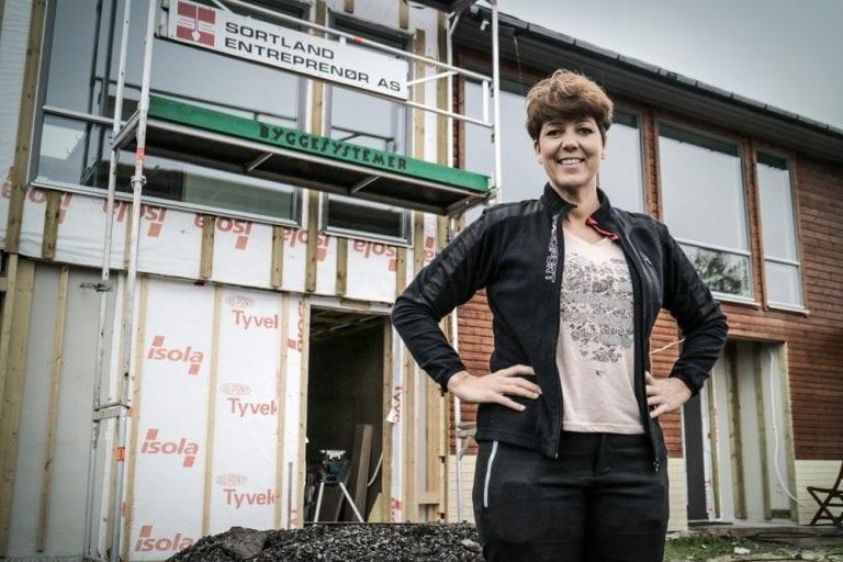 Bilde av dame foran et hus under bygging
