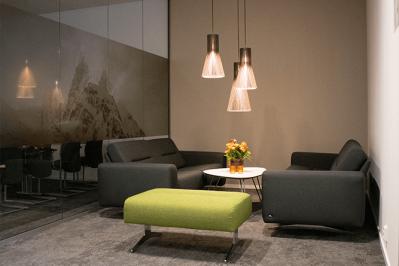 Lounge med 2 svarte sofaer og en grønn krakk